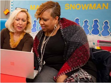 Two women look at laptop together in classroom
