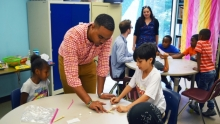 Quan Jones, a master's student at UVA studying to become a teacher, assists local English learners with building a marshmallow catapult