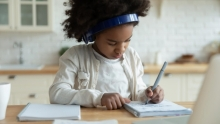 Young girl wearing headphones sits at a desk writing in a notebook