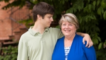 Adam Painter stands with one arm around his mom, Fay, looking in her direction.