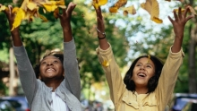 two girls smiling while tossing leaves into the air