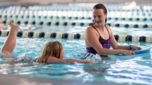 Lillie Neal and her young charge, a Special Olympian, work on swimming techniques at UVA's North Grounds Recreational Center.