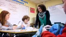 Teacher and middle school students interacting in a classroom setting