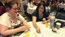 Teachers at a table playing with manipulative at the conference