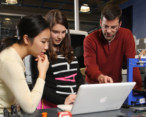 Teacher and students working on computer-aided design before printing